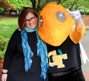woman with brown hair and glasses hugging Georgia Tech's mascot, Buzz